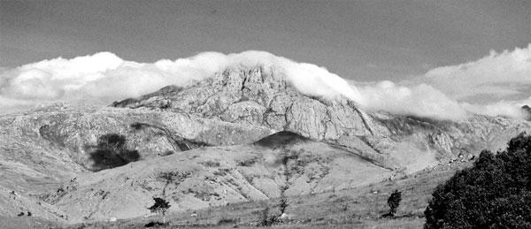Massif rocheux, nuages et feux de brousses